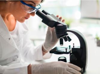 Forschung. Frau an Mikroskop.