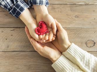 Dauerspende: zwei einander haltende Hände mit einem Herz in der Mitte