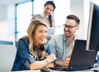 Erwachsene sitzen vor einem Laptop und lachen