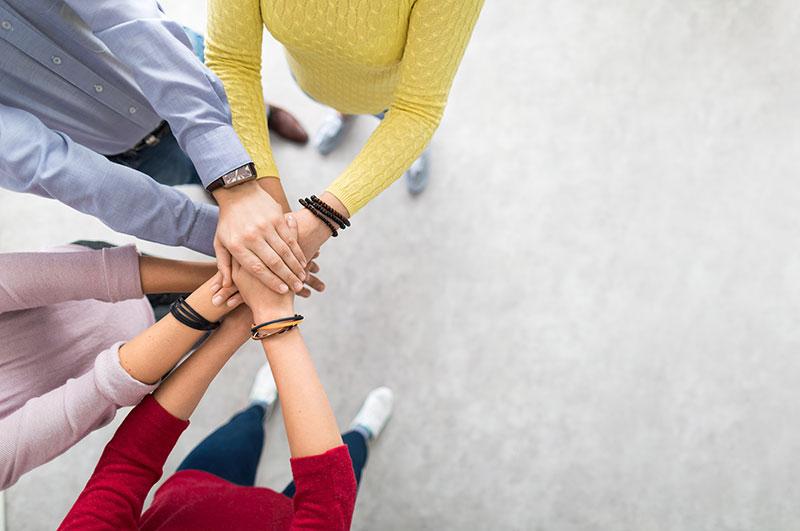 Vier Personen halten im Kreis ihre Handflächen übereinander
