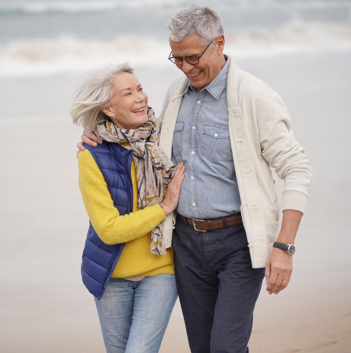 Älteres Pärchen geht Arm in Arm am Strand spazieren