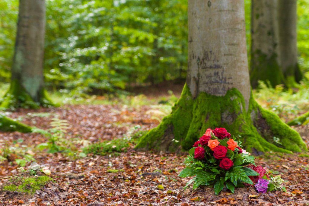 Ein Blumenstrauß liegt im Wald vor einem Baum