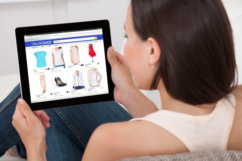 Frau hält Tablet in der Hand, auf welchem eine Shopping-Seite angezeigt wird