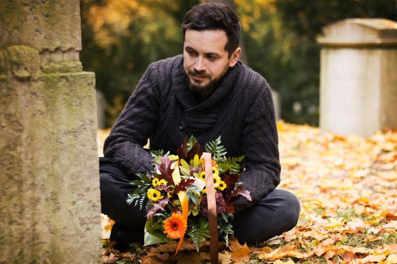 Ein Mann kniet auf dem Friedhof vor einem Grab. In seiner Hand hält er einen Kondolenzkranz